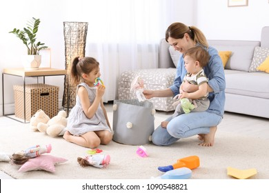 Housewife and children picking up toys after playing at home