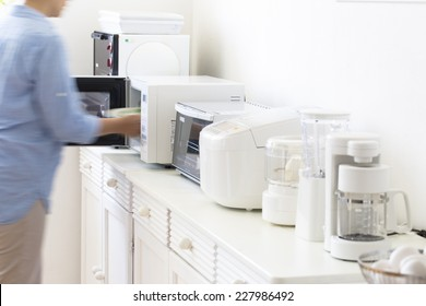 Housewife cooking in a small cooking appliances