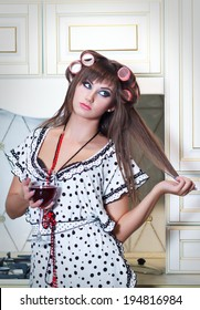Housewife with curlers and a glass of wine posing in the kitchen.