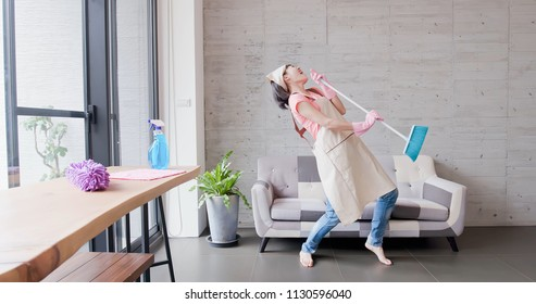 housewife dance happily and sing in the living room