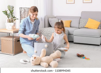 Housewife and daughter picking up toys after playing at home
