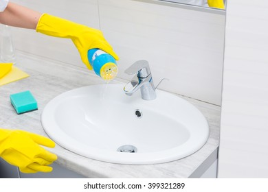 Housewife emptying a scouring powder into a hand basin from a plastic bottle with gloved hands in a health and hygiene concept