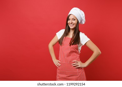 Housewife female chef cook or baker in striped apron, white t-shirt, toque chefs hat isolated on red wall background. Beautiful housekeeper woman standing with arms akimbo. Mock up copy space concept