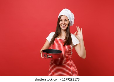Housewife female chef cook or baker in striped apron, white t-shirt, toque chefs hat isolated on red wall background. Housekeeper woman holding metal baking form for pie. Mock up copy space concept