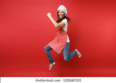 Housewife female chef cook or baker in striped apron white t-shirt, toque chefs hat isolated on red wall background. Full length portrait housekeeper woman jumping high up. Mock up copy space concept