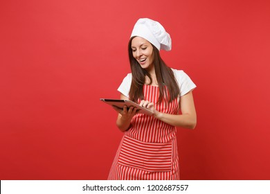Housewife female chef cook or baker in striped apron, white t-shirt, toque chefs hat isolated on red wall background. Fun housekeeper woman looking for recipe in tablet pc. Mock up copy space concept