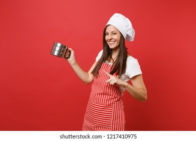 Housewife female chef cook or baker in striped apron, white t-shirt, toque chefs hat isolated on red wall background. Housekeeper woman hold metal iron sieve sifting flour. Mock up copy space concept