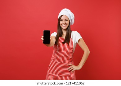 Housewife female chef cook or baker in striped apron t-shirt toque chefs hat isolated on red wall background. Woman hold cellphone with blank screen for promotional content. Mock up copy space concept