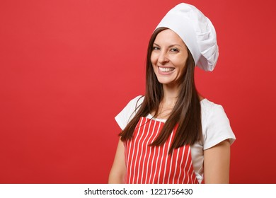 Housewife female chef cook or baker in red striped apron, white t-shirt, toque chefs hat isolated on red wall background. Close up portrait of housekeeper brunette woman. Mock up copy space concept