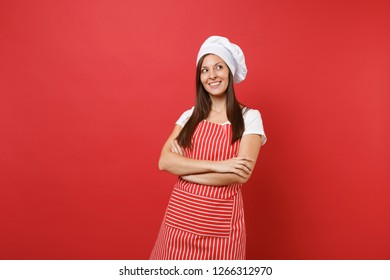 Housewife female chef cook or baker in striped apron, white t-shirt, toque chefs hat isolated on red wall background. Pretty young housekeeper woman holding hands crossed. Mock up copy space concept