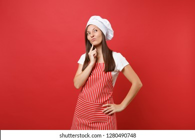 Housewife female chef cook or baker in striped apron, white t-shirt, toque chefs hat isolated on red wall background. Beautiful housekeeper woman put hand prop up on chin. Mock up copy space concept