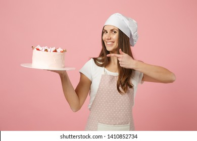 Housewife female chef cook confectioner or baker in apron white t-shirt, toque chefs hat hold in hand cake on stand plate isolated on pink pastel background in studio. Mock up copy space food concept