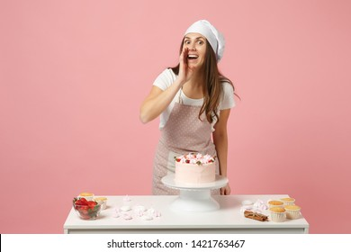 Housewife female chef cook confectioner or baker in apron white t-shirt, toque chefs hat cooking cake or cupcake at table isolated on pink pastel background in studio. Mock up copy space food concept