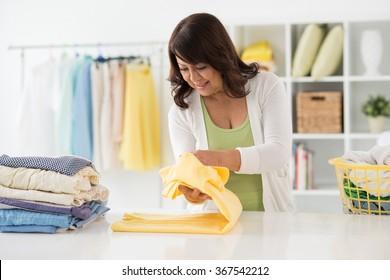Housewife folding freshly washed shirts