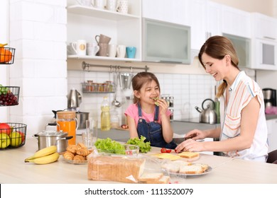 Housewife with her daughter preparing dinner on kitchen