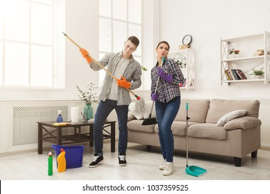 Housewife and her husband cleaning home and having fun together. Housekeeping, home cleaning and cleaning service concept