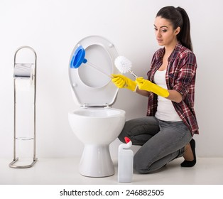 Housewife is holding brush and plunger. She is going to cleaning toilet.