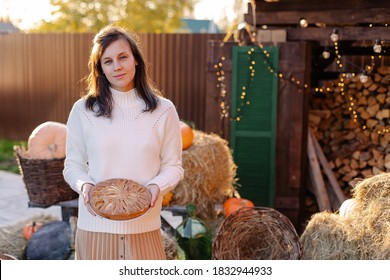 housewife holding homemade delicious pie for Thanksgiving. A woman is waiting for guests of family traditions. festive dinner treat. Girl happy smiling autumn portrait. country house  veranda outside