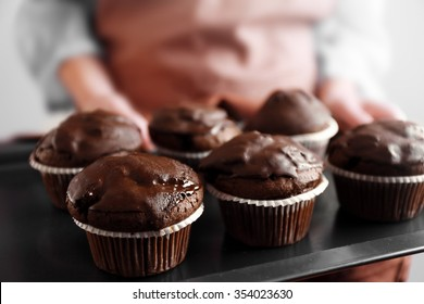 Housewife holding oven-tray with chocolate cupcakes, close up