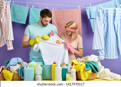 housewife and husband looking at spot T-shirt while standing behind table with clothes and bowl. service concept.isolated blue background. man and woman thinking about how wash dirty clothes