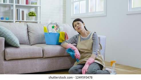 housewife kneeling down on the wooden floor holding cloth wearing gloves and apron resting. exhausted asian woman tired after doing housework prepared new year holidays. cleaning products in bucket
