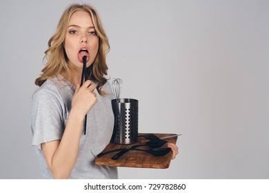 housewife licks tongs for cooking in hand holds kitchen utensils on a gray background