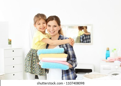 Housewife and little daughter with freshly washed towels in laundry room