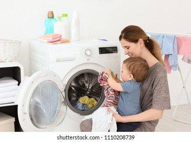 Housewife with little son doing laundry at home