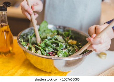 Housewife mixes salad in a large bowl with two wooden spoons