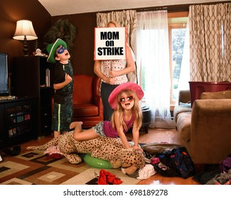 A housewife mother is under stress and tired of cleaning the house holding a funny Mom On Strike Sign with messy children for a discipline or parenting concept.