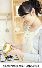 Housewife peeling a pear