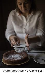 housewife preparing brownies on a dark wooden table