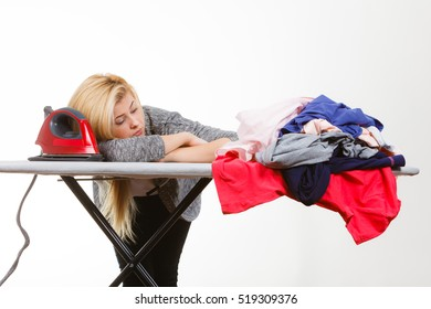 Housewife problems, tiredness concept. Sleepy bored woman lying on ironing board, having lot of clothes to iron. Studio shot on white background