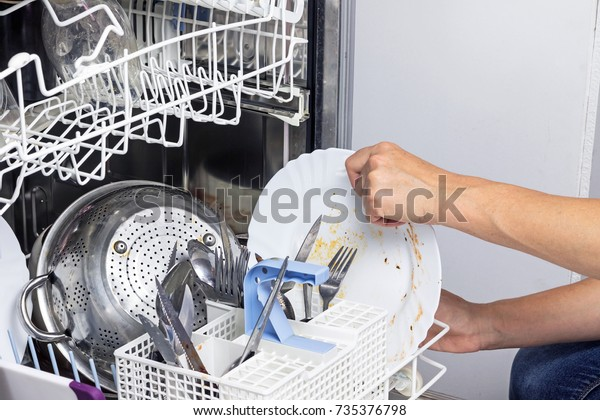 Housewife puts dirty dishes in the dishwasher. Horizontally.