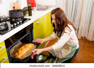 housewife putting apple pie to the oven on the kitchen at home