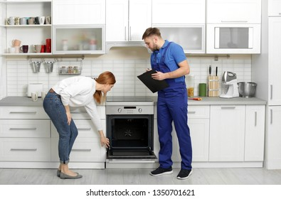 Housewife with repairman near modern oven in kitchen