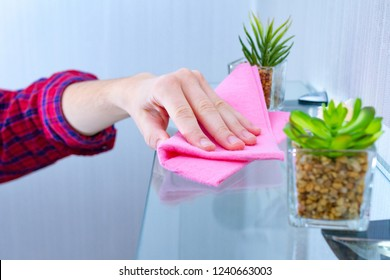 A housewife in a shirt is cleaning the house, wiping the dust from the shelf with a cleaning rag. Household chores