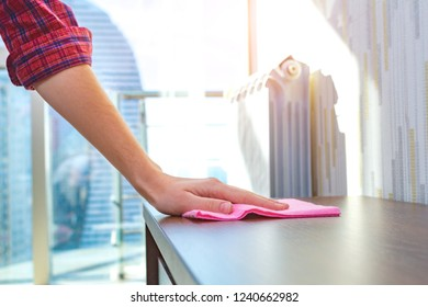 A housewife in a shirt cleans the house, wipes dust from the table with a cleaning rag. Household chores