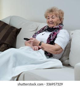 Housewife sitting on sofa and holding remote control