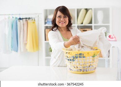 Housewife taking clean clothes out of basket