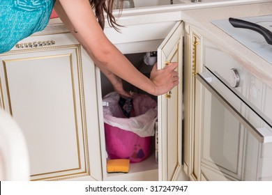 Housewife throwing out garbage in the kitchen opening a cupboard door under the sink to toss waste into the bin as she does the cooking