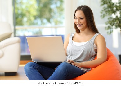 Housewife using a laptop at home sitting on an orange pouf in the living room at home