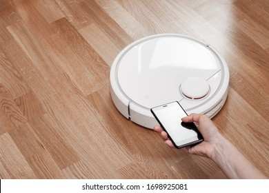 housewife using mobile to control robotic vacuum cleaner. robot controlled by voice commands to direct cleaning. Modern smart cleaning technology housekeeping.