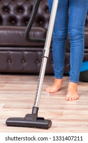 Housewife with a vacuum cleaner cleans the room in the house