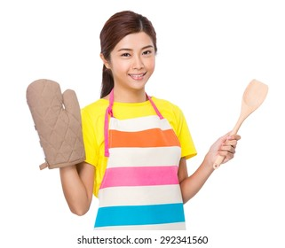 Housewife wear with oven gloves and hold with wooden ladle