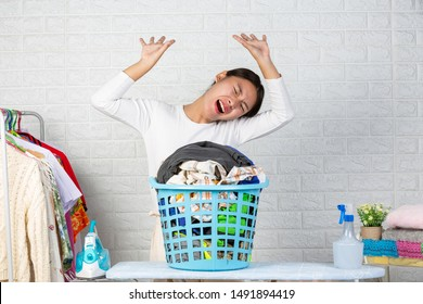 The housewife who is tiring is tired of the clothes in the basket with a white brick background.