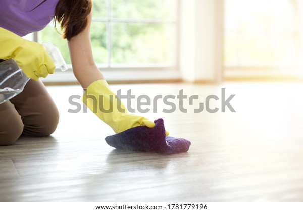 Housewife is wiping, cleaning, and disinfecting the floor. Asian young woman is happily doing housework.