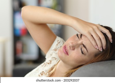 Housewife woman in a couch with headache and a hand on forehead