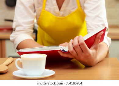 Housewife woman reading cookbook in kitchen. Female in apron at home.