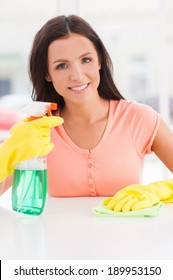 Housewife at work. Young beautiful woman in yellow gloves holding a rag and spray bottle while smiling at camera